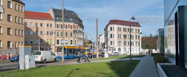 Man sieht einen Kreuzungsbereich mit Straßenbahn und Passanten, es stehen alte Häuser und ein neuer Bau mit Glasfront in diesem Areal.