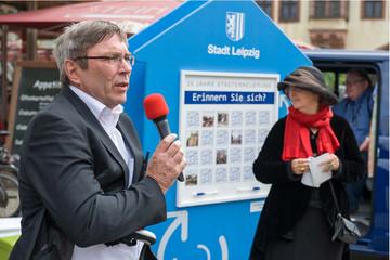 Bild wird vergrößert: Herr Gerkens und Frau Dubrau stehen draußen vor einer blauen Infowand. Herr Gerkens hat ein Mikrofon in der Hand und redet.