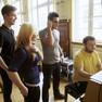Jugendliche stehen um ein Klavier. An diesem sitzt ein junger Mann in gelbem T-Shirt und spielt.