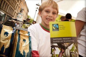 Bild wird vergrößert: Kind mit Fairtrade-Produkten