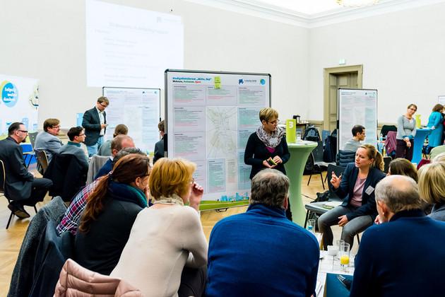 In einem Raum sitzen an Tischen mehrere Gruppen von Menschen beisammen und diskutieren miteinander. Im Raum stehen mehrere Tafeln mit Zetteln und Notizen.