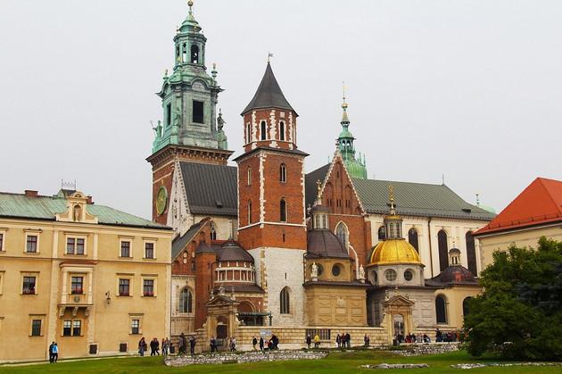 Wawel-Kathedrale mit rotem Turm und zwei Kupfertürmen eingefasst von gelben Gebäuden in Krakau