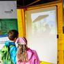 Kinder schauen sich am Stand des Verkehrs- und Tiefbauamtes bei der Ökofete den Erklärfilm zum Stadtraumkonzept erweiterte Innenstadt an.
