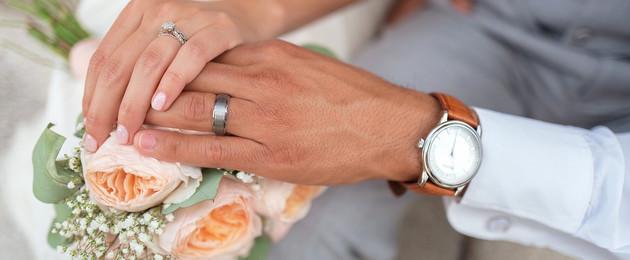 Die Hände einer Frau und eines Mannes liegen auf einem Blumenstrauß. Man erkennt im Hintergrund, dass die Frau ein weißes Kleid und der Mann einen grauen Anzug trägt. Beide tragen Eheringe.