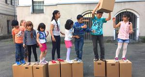 Kinder unterschiedlicher Herkunft stehen in einer Reihe auf Kartons und reichen siche einen Karton weiter.