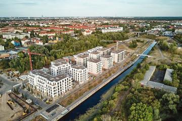Bild wird vergrößert: Blick über die neugebauten Wohngebäude direkt am Wasser am Lindenauer Hafen mit Baukränen, neuer Brücke und der Skyline der Stadt im Hintergrund.