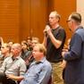 Blick ins Publikum. Ein Mann ist aufgestanden und spricht in ein Mikrofon. Neben ihm steht ein weiterer Mann im Jacket.