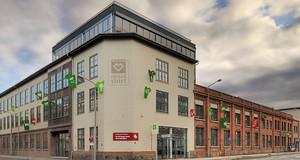 Blick auf den Hauptsitz von Spreadshirt in Leipzig-Plagwitz, über das Gebäude ziehen sonnenbeschienene Wolken