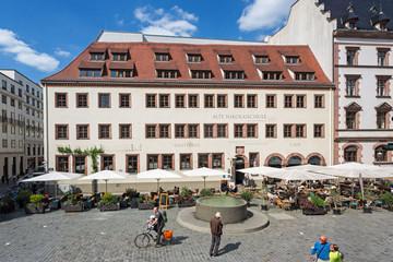 Bild wird vergrößert: Blick auf ein historiches Gebäude, die Nikolaischule Leipzig. Davor der Freisitz eines Restaurants, ein Brunnen und Passanten