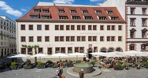 Blick auf ein historiches Gebäude, die Nikolaischule Leipzig. Davor der Freisitz eines Restaurants, ein Brunnen und Passanten