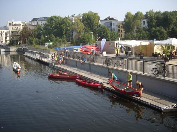 Die Abbildung zeigt den Stadthafen Leipzig bei bestem Wetter. Menschen lassen Boote ins Wasser