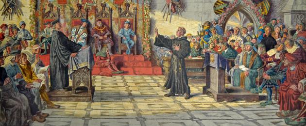 Luther und Eck stehen sich gegenüber und diskutieren. Viele Zuschauer sind im Raum.