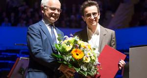 Heinrich Riethmüller übergibt Masha Gessen eine Urkunde und Blumen.
