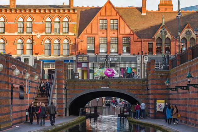 Kanal fließt in Birmingham unter einer roten Backsteinbrücke, welche oberhalb mit roten Backsteingebäuden bebaut ist. Diese Gebäude beherbergen gastronomische Einrichtungen.