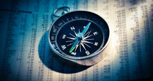 Ein Kompass liegt auf einem Blatt, auf dem tabellarisch Zahlen notiert sind.