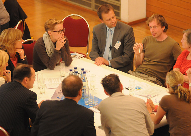 Menschen sitzen um einen großen, eckigen Tisch und diskutieren miteinander.