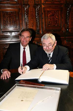 Städtepräsident Krakaus sitzt mit Stift in der Hand vor dem Goldenen Buch, daneben Oberbürgermeister Jung