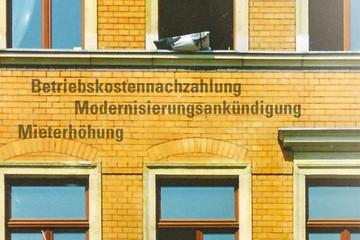 """Bild wird vergrößert: Kleiner Ausschnitt einer Altbaufassade. Zwischen zwei Stockwerken stehen untereinander sie Worte """"Betriebskostennachzahlung"""", """"Modernisierungsankündigung"""" und """"Mieterhöhung""""."""
