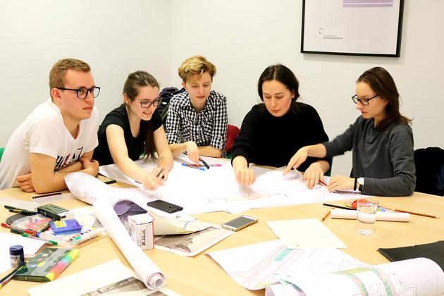 Studenten sitzen um einen Tisch und zeichnen Entwürfe