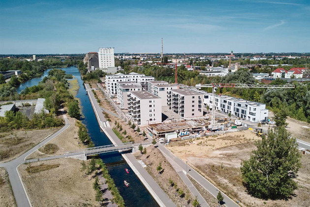 Blick über die neugebauten Wohngebäude direkt am Wasser am Lindenauer Hafen mit Kran, neuer Brücke und Speichergebäuden im Hintergrund.