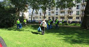 Mitarbeiter aus dem Projekt Blau-Gelbe-Engel bei der Müllbeseitigung auf einer Wiese