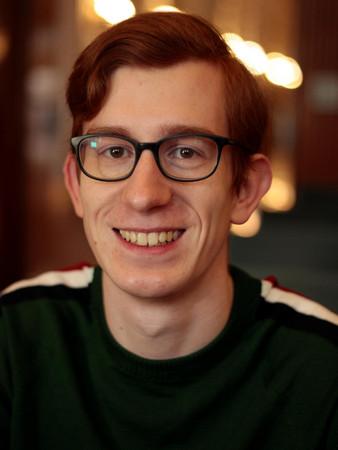 Quentin Kügler - Ein junger Herr mit Seitenscheitel und Brille lächelt ins Bild