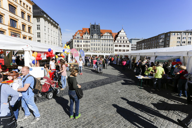 An den zahlreichen Ständen auf dem Leipziger Marktplatz stehen Besucher des Tages der Begegnung und unterhalten sich.