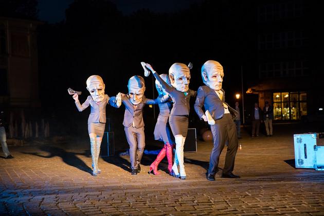 Fünf Schauspieler und Schauspielerinnen mit Anzug beziehungsweise Kostüm bekleidet tanzen auf einem städtischen Platz. Alle tragen als Maske einen überdimensionalen Kopf eines alten, faltigen Mannes mit Glatze.