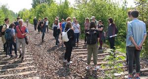 Eine Menschengruppe steht auf stillgelegten Gleisen und schaut sich um