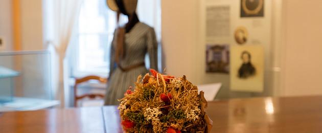 Blumenstrauß liegt auf dem Klavier im Museum des Schumann Hauses. Im Hintergrund steht eine Ausstellungspuppe mit historischer Kleidung.