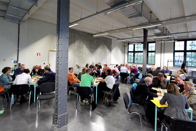 Blick in eine Halle, in der ca. 50 Menschen an verschiedenen Tischen sitzen.