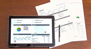 Auf einem Tisch liegen Blätter mit Statistiken und ein Tablet, auf dem ebenfalls Statistiken zu sehen sind.