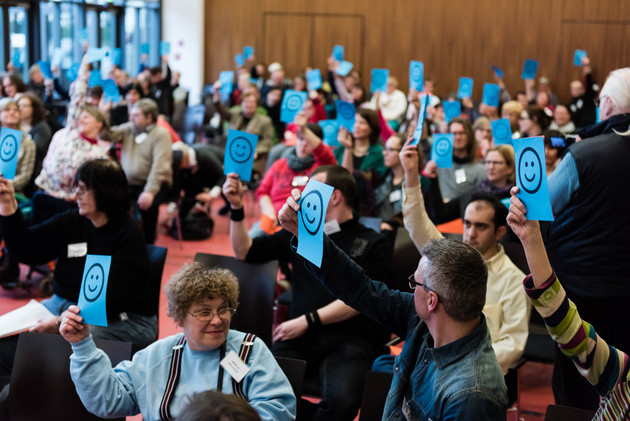 Ein Saal voller Menschen. Alle halten blaue Zettel mit einem lachenden Smiley darauf in die Höhe.