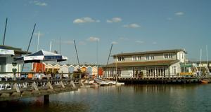 Hafenanlagen am Cospudener See mit Booten und einer Sitzterasse mit Besuchern