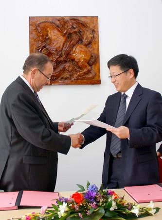 Professor Güldner (links) und Herr Zou unterzeichnen den Vertrag, der die Kooperation zwischen dem Städtischen Klinikum St. Georg und dem Nanjing Gulou Hospital verlängert