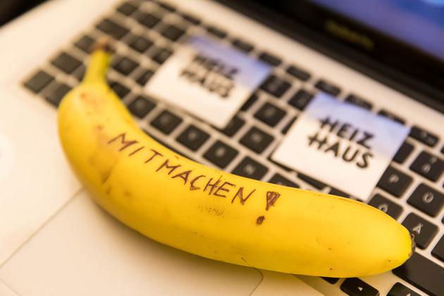 """Auf einer Laptoptastatur kleben Klebezettel mit dem Titel """"Heizhaus"""" drauf. Außerdem liegt eine Banane auf der Tastatur auf der Mitmachen! geschrieben steht."""