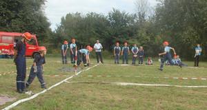 Angehörige der Jugendsfeuerwehr sprinten auf der Wettkampfstrecke bei der Disziplin Gruppenstafette in Richtung Ziel