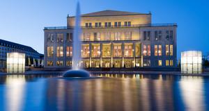 Außenansicht der Oper Leipzig zur blauen Stunde mit einer flachen Wasserfläche und einer Wasserfontäne davor.
