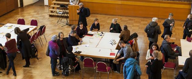Blick von oben in einen großen Raum. Menschen sitzen gruppenweise an mehreren Tischen zusammen.