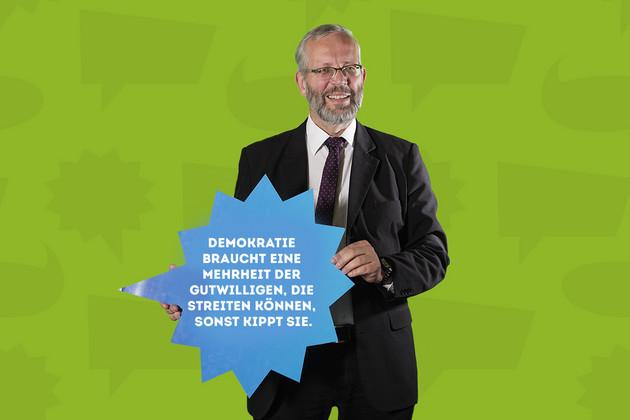 """Der Stadtrat Karsten Albrecht hält ein Schild mit dem Statement """"Demokratie braucht eine Mehrheit der Gutwilligen, die streiten können, sonst kippt sie.""""."""