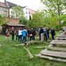 Auf einer Wiese steht eine Menschengruppe und spricht miteinander. Auf der Wiese sind Holzelemente installiert. Hinter der Wiese sind Häuser.