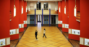 Eine hohe Halle mit schräg zueinander stehenden roten Säulen und Parkettboden. Zwei Frauen laufen durch die Halle.