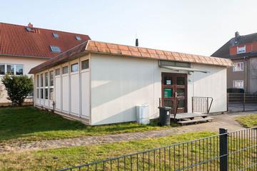 Bild wird vergrößert: Gebäude Ortsteilzentrum Rückmarsdorf. Kleiner Flachbau neben Wohnhäusern.