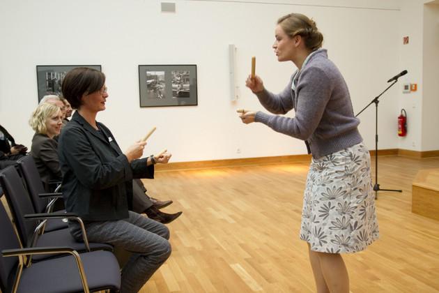Zwei Frauen blicken sich an. Eine steht. Eine sitzt. Beide haben Klanghölzer in den Händen. Im Hintergrund zu sehen: ein lächelndes Publikum.