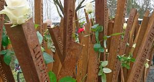 Rostige Stahlwinkel, in die die Namen und Lebensdaten der Opfer des KZ Außenlagers in Abtnaundorf eingeschnitten sind. Einige sind mit weißen Rosen geschmückt.