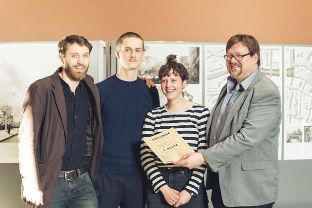 Drei Männer und eine Frau posieren für die Kamera, der Mann ganz rechts hält eine Urkunde hoch.