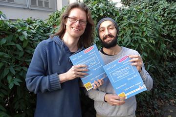 """Bild wird vergrößert: Oliver Reiner und Soubhi Shami von der """"VILLA"""" mit zwei Exemplaren ihres Sprachlernbuches"""