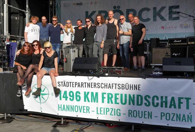 """Bühne mit dem Banner """"Städtepartnerschaftsbühne"""", auf der 14 Akteure für ein Gruppenbild posieren, darunter die drei Musiker der Leipziger Band Lizard Pool."""