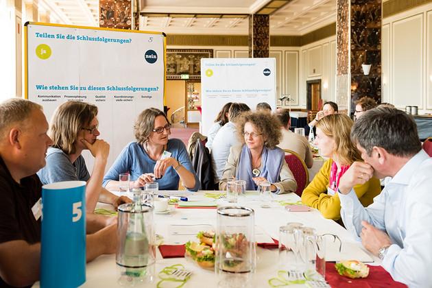 8 Menschen sitzen an einem Tisch und diskutieren interessiert