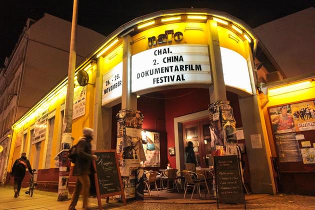 """Eingangsbereich der nato, Aufnahme bei Nacht, beleuchtete Anzeigetafel mit Schriftzug """"chinesisches Dokumentarfilmfestival"""""""